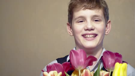 cheerful boy with a bouquet of flowers.