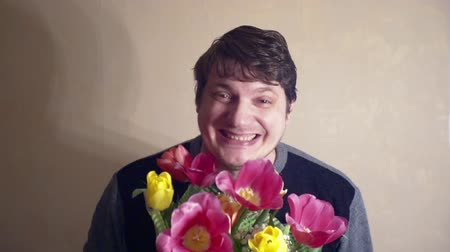 bouquets : Portrait of a funny cheerful man with a bouquet of flowers