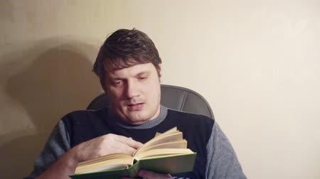 portrait of middle-aged man who is bored sitting with a book