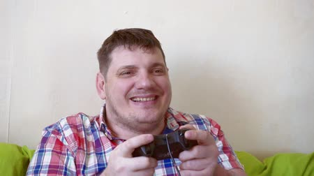 man with a joystick in his hands spends time sitting on the couch