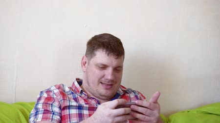 man spends time sitting on a sofa with a smartphone.