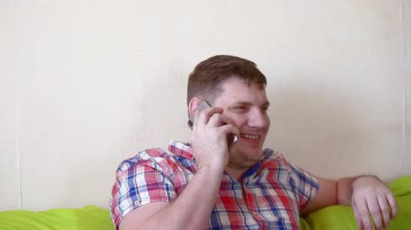 man spends time sitting on a sofa with a smartphone Stock mozgókép