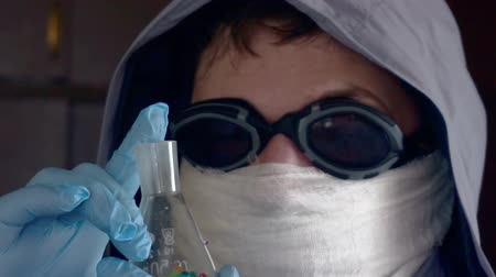 любопытство : researcher in a protective uniform holds a dirty glass tube