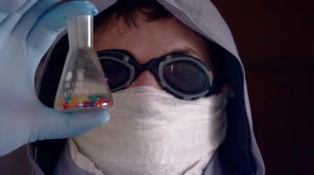 microbiologia : researcher in a protective uniform holds a dirty glass tube