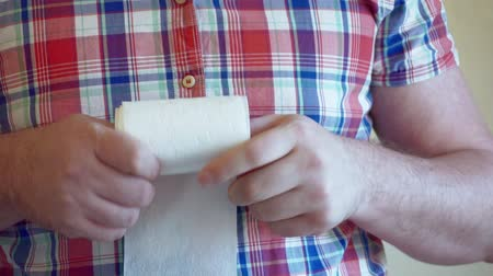 Mens hands unwind a roll of white toilet paper.