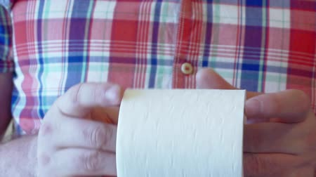 higiênico : Mens hands unwind a roll of white toilet paper.
