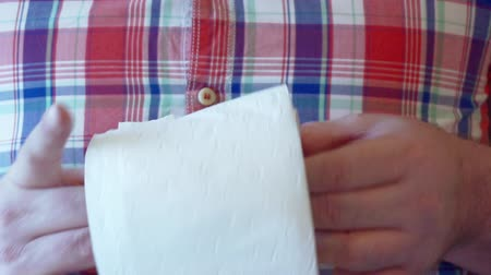 semmeln : Mens hands unwind a roll of white toilet paper.