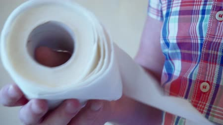 toeletta : Mens hands unwind a roll of white toilet paper