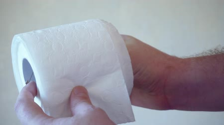 rulolar : Mens hands unwind a roll of white toilet paper