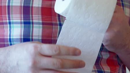 Mens hands unwind a roll of white toilet paper