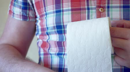 tekercselt : male hands hold a roll of white toilet paper