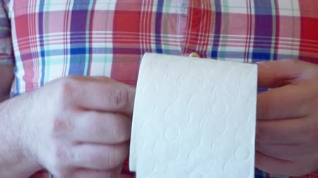 male hands hold a roll of white toilet paper