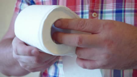 higiênico : male hands hold a roll of white toilet paper.