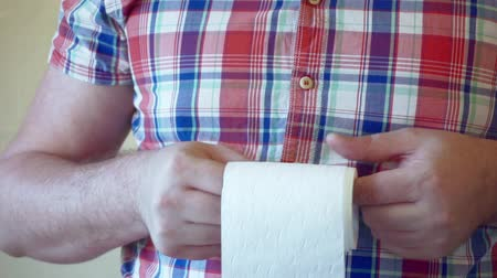 male hands hold a roll of white toilet paper.