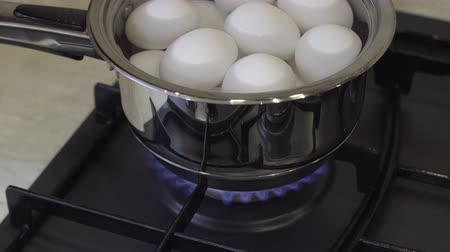 Turning on gas stove for boiling eggs in the kitchen