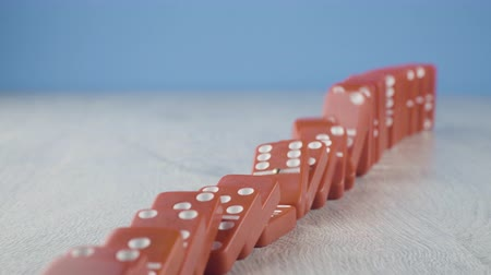 continuidade : Domino effect - a series of red dominoes falling down the chain on blue background Vídeos