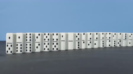 continuity : Domino effect - a series of dominoes falling down the chain on blue background
