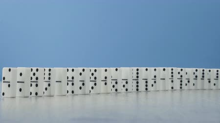continuidade : Domino effect - a series of dominoes falling down the chain on blue background