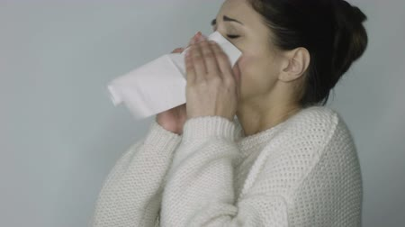 horečka : girl in a white sweater sneezes