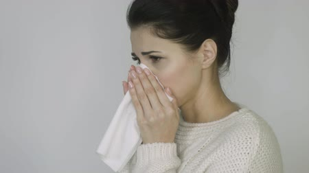 influenza background : girl in a sweater sneezes on a white background Stock Footage