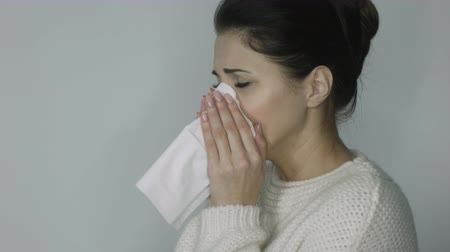 influenza background : ill girl in a sweater sneezes Stock Footage