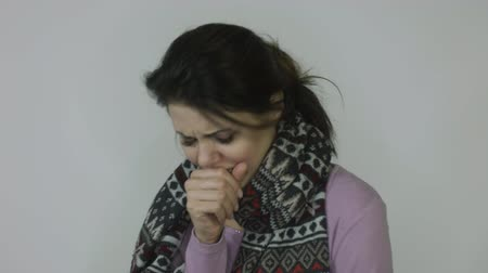 influenza : Ill girl with runny nose in scarf with temperature coughs in front of white background
