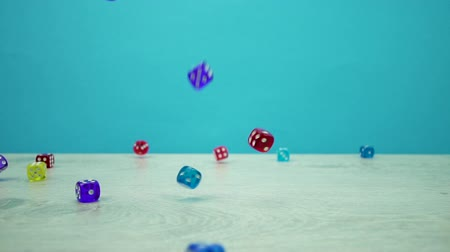 kości do gry : Slow-mo shot of multicolored dice fall on a aquamarine background
