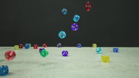 kości do gry : Slow motion shot of multicolored dice fall on a black background Wideo