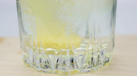 analgésico : Close-up shot of An effervescent yellow pill against pain falls into a glass and dissolves slow-motion shot of aspirin on a colored background
