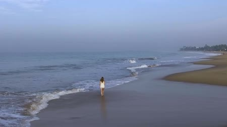 hikkaduwa : aerial shot the girl is walking alone on the beach with ocean waves