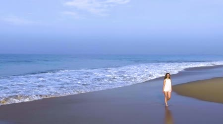 Канкун : aerial shot the girl is walking alone on the ocean beach in tropical country