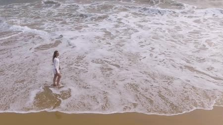 hikkaduwa : A young girl in white dress is walking on beach with ocean waves