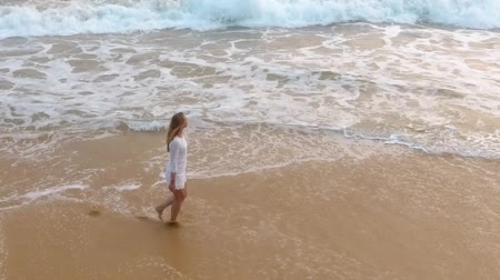 Канкун : A young girl in a short white dress is walking on sandy beach in hikkaduwa Стоковые видеозаписи
