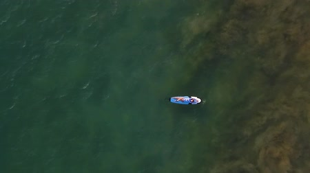 hikkaduwa : pretty girl lies on a surf on ocean waves copter view with beach