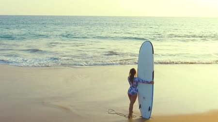 hikkaduwa : a girl on the beach stands with a surf, preparing to go into the water, a sandy beach and ocean waves Stock Footage