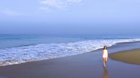 hikkaduwa : Slow motion aerial shot the girl is walking alone on the ocean beach in tropical country