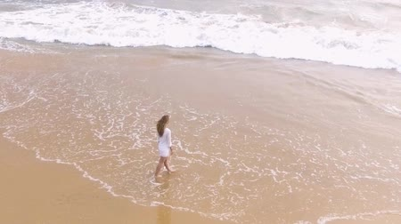 Канкун : Slow motion aerial shot A young girl in a short white dress is walking along the sandy beach in the tropics, near the ocean