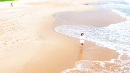 hikkaduwa : Drone shot of A young girl in a short white dress is walking along the sandy beach in the tropics, near the ocean, and wets her feet in the water sri lanka, hikkaduwa