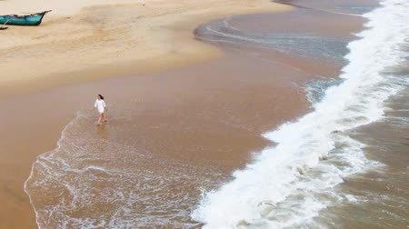 hikkaduwa : Slow motion aerial shot A you happy girl in a short white dress is walking along the sandy beach in the tropics, near the ocean, and wets her feet in the water sri lanka, hikkaduwa
