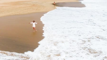 Канкун : Slow motion aerial shot Top view of A young girl in a short white dress is dancing on the sandy beach in hikkaduwa, sri lanka, near the ocean, and wets her feet in the water