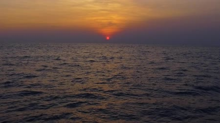 Орегон : Slow motion aerial shot Tropical sunset. Red sun sets over the ocean, the sea waves in the evening light, beautiful afterlight