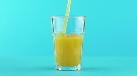 faceted : Slow motion close-up shot of fruit orange multifruit juice cold beverage drink pooring into faceted glass on colored blue background in studio Stock Footage