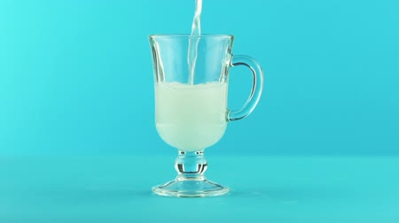 limonádé : Slow motion close-up shot of fruit fizzy lemonade soda cold beverage drink pooring into latte glass mug blue background in studio