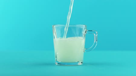 limonádé : Slow motion close-up shot of fruit fizzy lemonade soda cold beverage drink pooring into glass mug with rounded handle blue background in studio