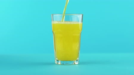 sports nutrition : 4K close-up shot of fruit fizzy orange cold beverage drink pooring into faceted glass on colored blue background in studio