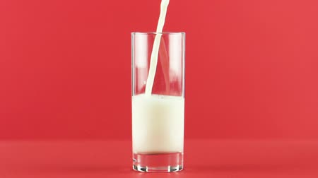 mléčný : Slow motion close-up shot of cold diary milk cold beverage drink pooring into glass red background in studio