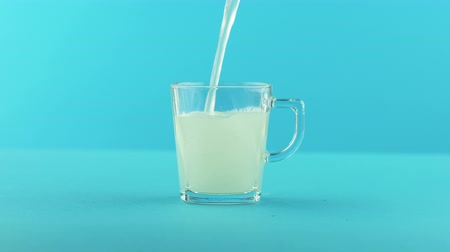 fehér háttér : 4K close-up shot of yellow lemon fizzy lemonade soda cold beverage drink pooring into glass mug with handle blue background in studio Stock mozgókép