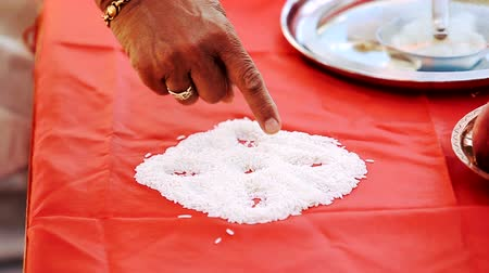 sherwani : Hindu man touches rice whih lies on the red tablecloth