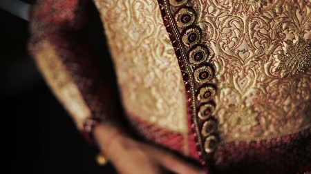 bengali : Close-up of mans hands buttoning up Hindu wedding suit Stock Footage
