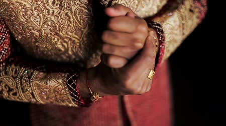 bengali : Indian man in wedding suit holds his hands together